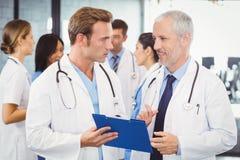 2 доктора смотря доску сзажимом для бумаги и обсуждая в больнице Стоковая Фотография