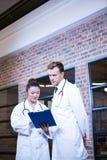 2 доктора смотря доску сзажимом для бумаги и обсуждая около библиотеки Стоковые Фото