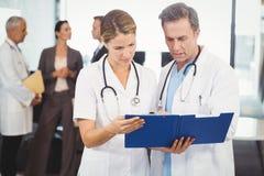 2 доктора смотря доску сзажимом для бумаги и обсуждая Стоковое Изображение RF
