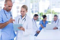 2 доктора смотря доску сзажимом для бумаги пока их работа коллег Стоковые Фото