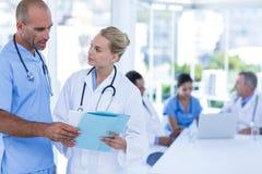 2 доктора смотря доску сзажимом для бумаги пока их работа коллег Стоковая Фотография