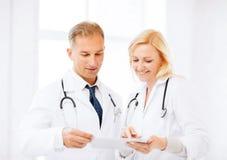 2 доктора смотря ПК таблетки Стоковое Изображение