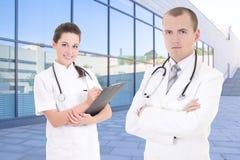 2 доктора стоя против современного здания больницы Стоковые Изображения