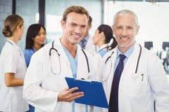 2 доктора с доской сзажимом для бумаги в больнице Стоковая Фотография RF