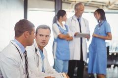 2 доктора с доской сзажимом для бумаги и обсуждать Стоковые Фотографии RF