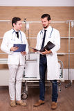 2 доктора с папками в руках в комнате спасения больницы говорят Стоковое Изображение RF