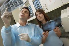 2 доктора Looking На Рентгеновский снимок Рапорт Стоковые Фотографии RF