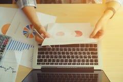 документы бизнес-леди на таблице офиса с портативным компьютером Стоковое фото RF