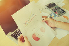 документы женщины на таблице офиса с портативным компьютером и диаграммой b Стоковое Изображение RF