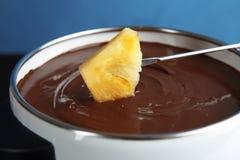 Окунать ананас в бак с вкусным фондю шоколада стоковое фото rf