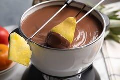Окунать грушу в бак с фондю шоколада на таблице стоковые фото