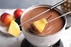Окунать грушу в бак с фондю шоколада стоковое фото