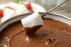 Окунать зефир в бак с вкусным фондю шоколада стоковое фото