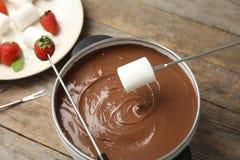 Окунать зефир в бак с вкусным шоколадом стоковые изображения