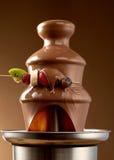 Окунать свежие фрукты в фонтан шоколада стоковые фотографии rf