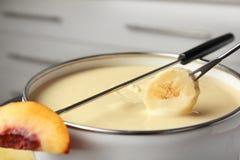 Окунать свежий банан в бак с фондю шоколада стоковые фотографии rf