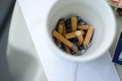Окурки в пластичной чашке Стоковая Фотография RF