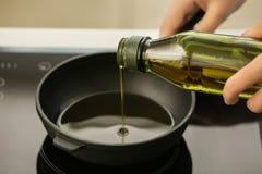 Оливковое масло женщины лить в сковороду на плите стоковое изображение rf