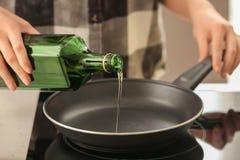 Оливковое масло женщины лить в сковороду на плите стоковая фотография rf