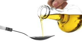 Оливковое масло женщины лить от стеклянного кувшина в ложку на белой предпосылке стоковые изображения