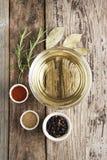 Оливковое масло и различные специи onwooden деревенская предпосылка: розмариновое масло, паприка, черный перец Взгляд сверху стоковая фотография
