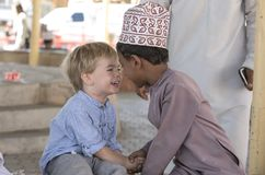 Оманский мальчик делая друзей с европейским мальчиком стоковое фото rf
