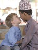 Оманский мальчик делая frineds с европейским мальчиком стоковые изображения