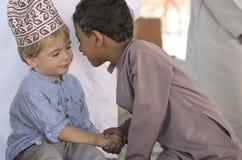 Оманский мальчик делая frineds с европейским мальчиком стоковая фотография rf