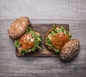 2 домашних бургера с цыпленком в соусе мустарда, arugula, томатах на разделочной доске на деревянном деревенском конце взгляд све Стоковое Изображение