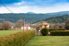 дома в деревне на зеленых полях и изгороди под пасмурной синью sk Стоковые Изображения