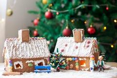 2 дома пряника, дерево и люд сидя на стенде, wint Стоковое Изображение