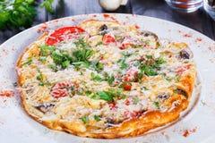 Омлет с кусками ветчиной, грибами, зелеными цветами, сыром и томатом на темной деревянной предпосылке стоковые изображения