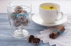 домодельные здоровые помадки с семенами сезама и кокосом в стекле, циннамоном, травяным чаем на деревянной предпосылке Стоковые Фотографии RF