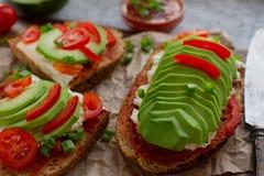 домодельные здравицы авокадоа на плавленом сыре хлеба рож, томатов, scallions, перца и Стоковое фото RF