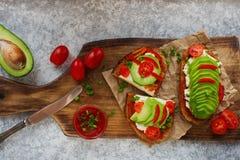 домодельные здравицы авокадоа на плавленом сыре хлеба рож, томатов, scallions, перца и Стоковые Изображения RF