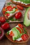 домодельные здравицы авокадоа на плавленом сыре хлеба рож, томатов, scallions, перца и Стоковая Фотография RF