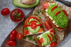 домодельные здравицы авокадоа на плавленом сыре хлеба рож, томатов, scallions, перца и Стоковые Изображения