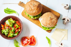 2 домодельных бургера говядины с яичком и салатом на деревянной таблице Стоковое Изображение