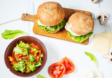 2 домодельных бургера говядины с яичком и салатом на деревянной таблице Стоковая Фотография