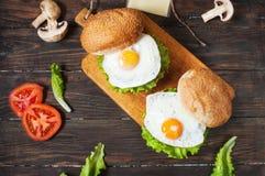 2 домодельных бургера говядины с яичком на деревянной таблице Стоковое Изображение