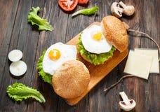 2 домодельных бургера говядины с яичком на деревянной таблице Стоковая Фотография