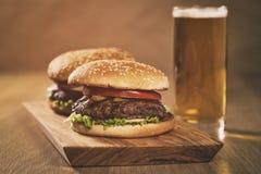 2 домодельных бургера на прованской доске на таблице дуба с пивом Стоковые Изображения