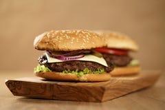2 домодельных бургера на прованской доске на таблице дуба Стоковые Изображения RF