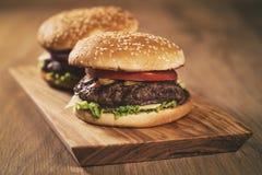 2 домодельных бургера на прованской доске на таблице дуба Стоковые Фото