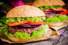 2 домодельных гамбургера с свежим зеленым салатом, томатами и красными луками Стоковое фото RF