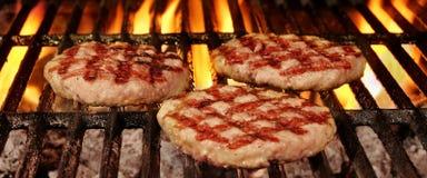 3 домодельных коричневенных бургера на горячем пламенеющем гриле BBQ Стоковая Фотография