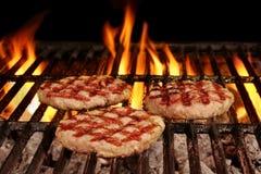 3 домодельных коричневенных бургера на горячем пламенеющем гриле BBQ Стоковое фото RF