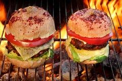 2 домодельных Cheeseburgers на пламенеющем гриле BBQ Стоковое фото RF