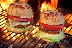 2 домодельных Cheeseburgers на пламенеющем гриле BBQ Стоковое Изображение
