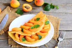 Омлет абрикосов Soufflé Омлет заполненный с свежими кусками абрикоса и украшенный с листьями мяты на белой плите Стоковые Изображения